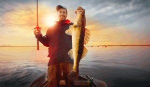 Man holding fish and rod on a boat in the water with sunset behind him
